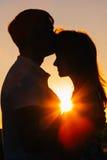 站立和亲吻在背景夏天草甸日落的浪漫剪影夫妇 免版税图库摄影