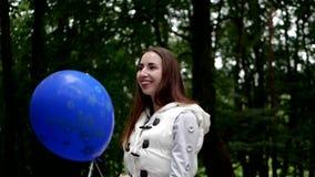 站立和使用与一个气球的年轻女人在一个森林里在春天 影视素材