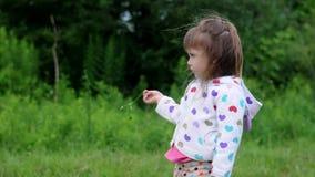 站立和使用与草的俏丽的女孩 影视素材
