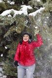 站立和使用在多雪的分支下的黑发土耳其妇女 库存照片