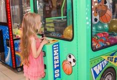 站立和使用在室内游乐园的小女孩 免版税图库摄影
