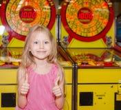 站立和使用在室内游乐园的小女孩 免版税库存照片