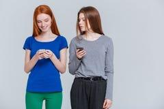 站立和使用手机的两个微笑的沮丧的少妇 免版税库存照片