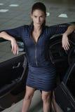 站立和倾斜她的手肘的确信的妇女对一个开放车门 免版税库存图片