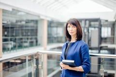 站立和做名单的成熟女实业家画象在办公室 免版税库存照片