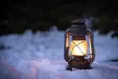 站立和发光在雪的灯笼在夜间 免版税图库摄影