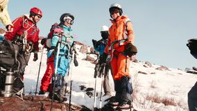 站立和喝从热水瓶的一个小组登山人茶 他们谈,放松和准备攀登山 股票视频