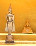 站立和坐在寺庙的两金黄菩萨雕象 库存图片