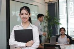 站立和微笑与colleage的领导年轻亚裔女商人在会议室背景中 库存照片