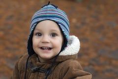 站立和微笑在秋天公园的小男孩 免版税库存图片