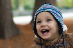 站立和微笑在秋天公园的小男孩 免版税库存照片