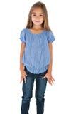 站立和微笑对照相机的逗人喜爱的小女孩 免版税库存图片