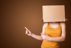 站立和打手势与在他的头的一个纸板箱的女孩 免版税图库摄影