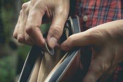 站立和拿着与钱包的特写镜头妇女金钱硬币 免版税图库摄影