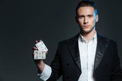 站立和拿着两张纸牌的严肃的年轻人魔术师 库存照片