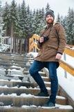 站立和拿着在台阶的快乐的人照相机在冬天 库存照片