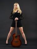 站立与声学吉他的女性 免版税库存照片