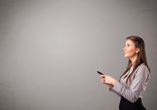站立和拿着有拷贝空间的小姐一个电话 免版税库存图片