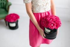站立和拿着有桃红色玫瑰的女孩黑匣子 时尚样式演播室画象 古色古香的扶手椅子被雕刻的内部豪华 免版税库存照片