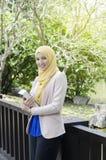 站立和拿着笔记本的Muslimah妇女 免版税库存照片