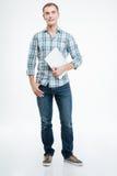 站立和拿着膝上型计算机的英俊的微笑的年轻人 库存照片