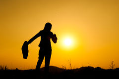 站立和拿着袋子的女商人在日落剪影 免版税库存图片