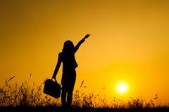 站立和拿着袋子的女商人在日落剪影 免版税图库摄影