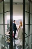 站立和握在阳台的迷人的婚礼夫妇手 回到视图 免版税库存图片