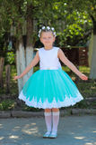 站立和摆在自然背景,有人造花花圈的孩子的礼服的美丽的小女孩在她的头的 免版税库存图片