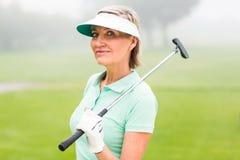 站立和摇摆她的俱乐部的高尔夫球运动员微笑对照相机 免版税库存照片