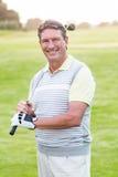 站立和摇摆他的俱乐部的高尔夫球运动员微笑对照相机 库存照片