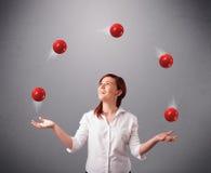 站立和玩杂耍与红色球的女孩 免版税库存图片