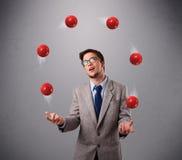 站立和玩杂耍与红色球的年轻人 库存图片
