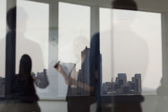 站立和看在玻璃墙的另一边的三个商人一个白板 免版税库存照片