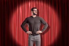 站立和看用在臀部的手的便服的年轻人,在聚光灯在红色阶段帷幕附近 免版税库存图片