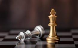 站立和落在棋盘的金国王 免版税库存图片