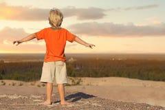 站立和观看在沙子山的男孩日落 免版税库存图片
