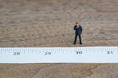 站立和认为在措施磁带上的微型商人在n 免版税库存照片