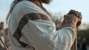 站立和调查距离的中世纪衣裳的老异教徒 免版税库存图片