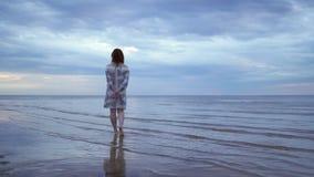 站立和走在前景和享用自然天空-惊人黑暗风景的一件白色礼服的年轻女人女孩 股票录像
