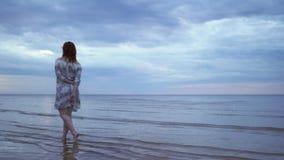 站立和走在前景和享用自然天空-惊人黑暗风景的一件白色礼服的年轻女人女孩 股票视频