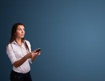 站立和键入在她的有拷贝空间的电话的少妇 库存图片
