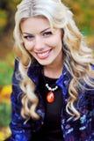 站立在一个公园的美丽的典雅的微笑的妇女在秋天 免版税图库摄影