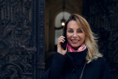 站立在一个华丽历史的门道入口的时髦的白肤金发的妇女 免版税库存照片
