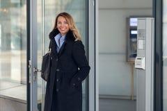站立在一个商业大厦的大厅的可爱的女实业家 免版税库存照片