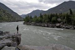 站立在一个大岩石的人涂了他的在山河的胳膊 免版税库存图片