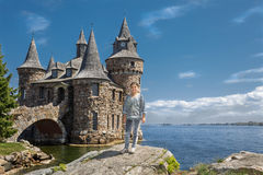 站立在一个大岩石的小女孩在湖附近反对老葡萄酒城堡 免版税图库摄影