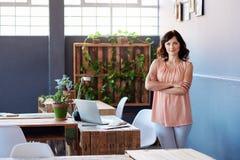 站立在一个大现代办公室的确信的年轻女实业家 库存图片