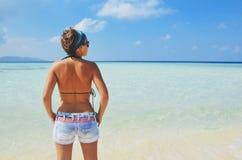 站立在一个完善的明信片热带海滩的牛仔裤的热的女孩 免版税库存图片