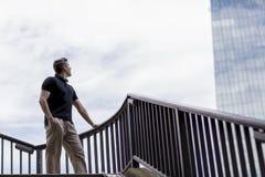 站立在一个室外楼梯间和看摩天大楼的人 库存图片